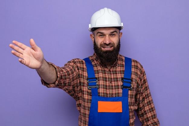 Construtor barbudo com uniforme de construção e capacete de segurança, olhando para a câmera, sorrindo alegremente, levantando o braço e acenando com a mão em pé sobre o fundo roxo