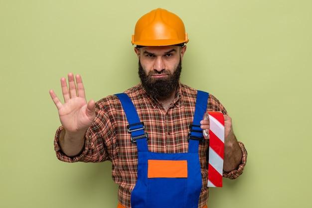 Construtor barbudo com uniforme de construção e capacete de segurança segurando fita adesiva, olhando com uma cara séria, fazendo gesto de parada com a mão