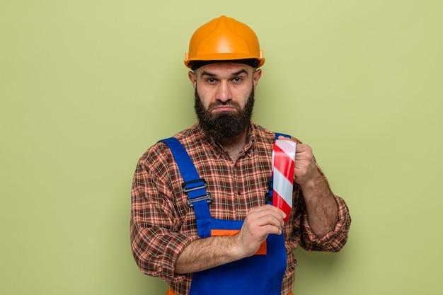 Construtor barbudo com uniforme de construção e capacete de segurança segurando fita adesiva, olhando para a câmera confuso em pé sobre um fundo verde