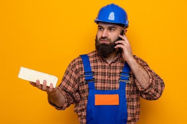 Construtor barbudo, com uniforme de construção e capacete de segurança, segurando um tijolo, parecendo confuso enquanto fala no celular, em pé sobre um fundo laranja