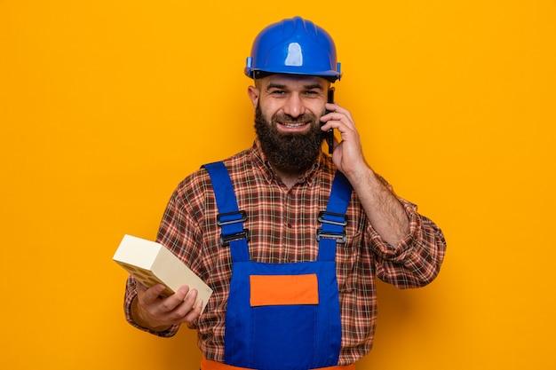 Construtor barbudo, com uniforme de construção e capacete de segurança, segurando um tijolo, sorrindo alegremente enquanto fala ao telefone móvel em pé sobre um fundo laranja