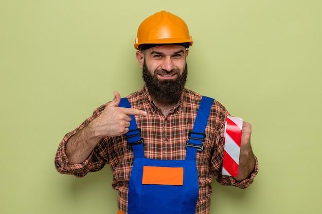 Construtor barbudo com uniforme de construção e capacete de segurança segurando uma fita adesiva apontando com o dedo indicador para ela, sorrindo alegremente