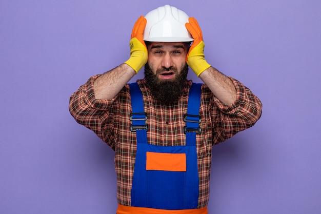 Construtor barbudo com uniforme de construção e capacete de segurança usando luvas de borracha, olhando para a câmera, confuso e preocupado, de mãos dadas na cabeça em pé sobre um fundo roxo