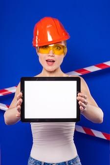Construtor bonita mulher de camisa branca, cinto de construtor, capacete, óculos de construtor, shorts jeans e snickers segurar tablet vazio