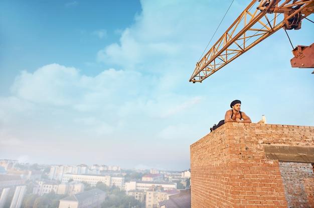 Construtor cansado e bonito no chapéu deitado na parede de tijolos no alto e descansando. desviando o olhar. céu azul com nuvens na temporada de verão em segundo plano. leite e pão próximos.