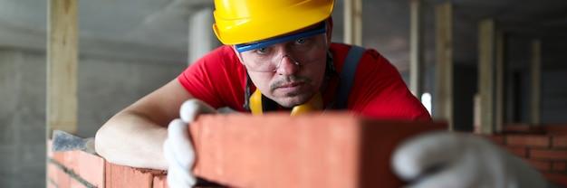 Construtor coloca cuidadosamente o tijolo vermelho na alvenaria