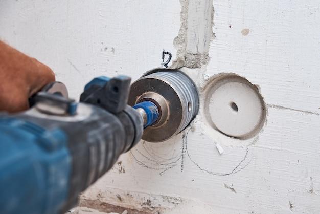 Construtor com broca de martelo perfurando orifício na parede