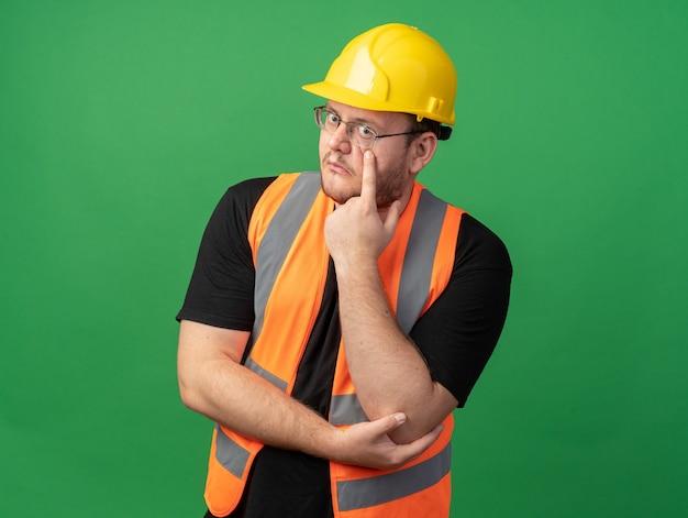Construtor com colete de construção e capacete de segurança olhando para a câmera confuso, apontando com o dedo indicador para o olho em pé sobre o verde