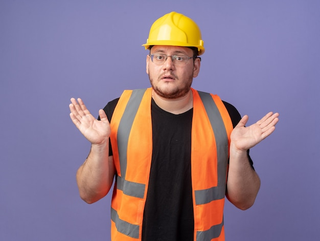 Construtor com colete de construção e capacete de segurança olhando para a câmera confuso, estendendo os braços para os lados de pé sobre o azul