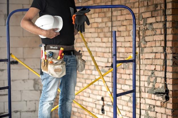 Construtor com ferramentas de construção no canteiro de obras