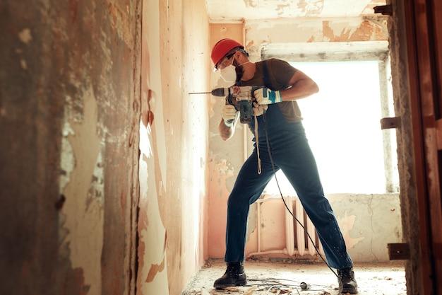 Construtor com perfurador faz furos na parede de concreto