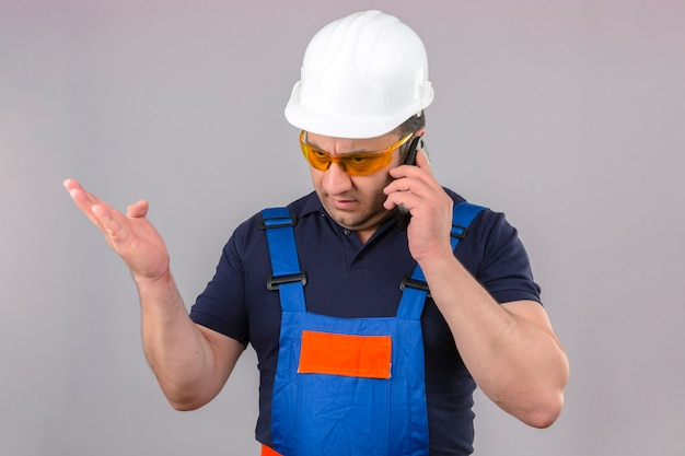 Construtor com raiva de meia idade homem vestindo uniforme de construção e capacete de segurança falando no telefone móvel irritado e frustrado sobre parede branca isolada