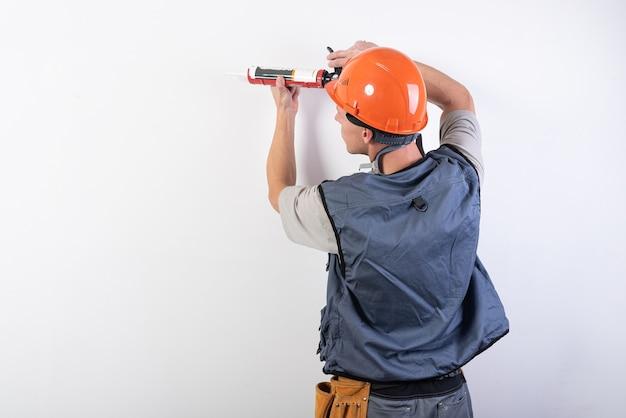 Construtor com selante. com roupa de trabalho e capacete. sobre um fundo cinza claro. para qualquer propósito.