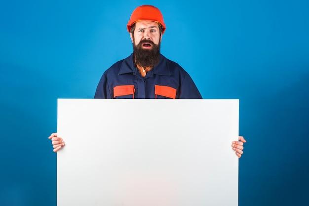 Construtor confuso com banner de publicidade vazio. trabalhador barbudo com roupas de proteção mostra a placa de sinal em branco pronta para o seu texto.