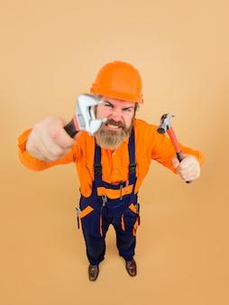 Construtor da indústria de construção de ferramentas de reparo com ferramentas de reparo homem barbudo em trabalhador de capacete de construção