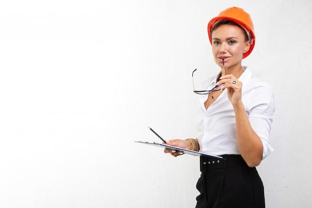 Construtor da mulher no capacete no fundo branco isolado