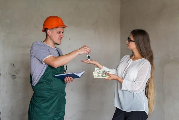 Construtor dando chaves de apartamento para mulher dando dinheiro