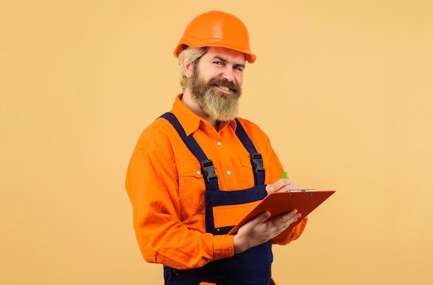 Construtor de capacete e macacão fazendo anotações na área de transferência. trabalhador da construção civil ou reparador com pasta.