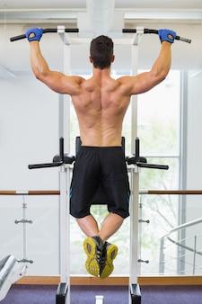 Construtor de corpo masculino fazendo pull ups no ginásio