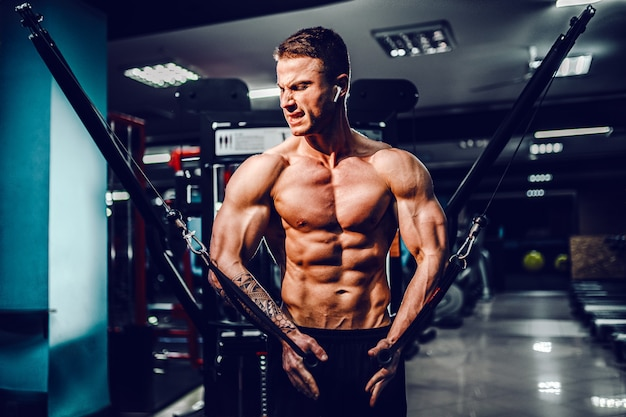 Construtor de corpo muscular malhando na academia fazendo exercícios com mosca no peito na máquina de cabos de arame