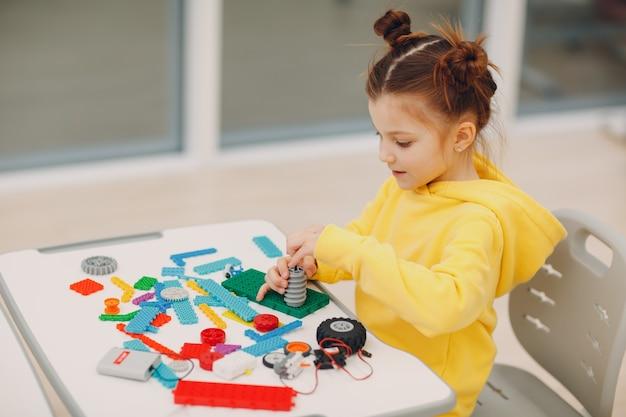Construtor de criança sorridente verificando brinquedo técnico infantil construtor de robótica montar robô