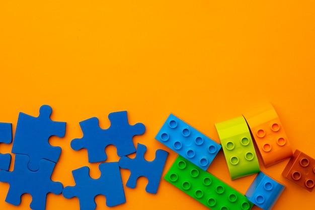 Construtor de crianças de brinquedo na vista superior do fundo amarelo