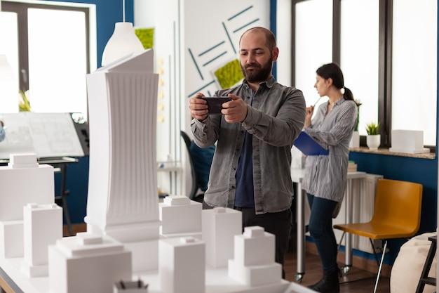 Construtor de design olhando para smartphone para projeto de engenheiro de estrutura arquitetônica em pé em ...