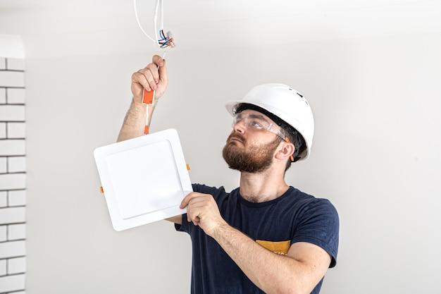 Construtor de eletricista com trabalhador de barba em um capacete branco no trabalho, instalação de lâmpadas em altura. profissional de macacão com uma broca no local de reparo.