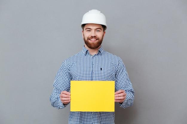 Construtor de homem barbudo alegre segurando papel em branco