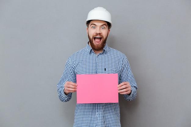 Construtor de homem barbudo feliz segurando papel em branco