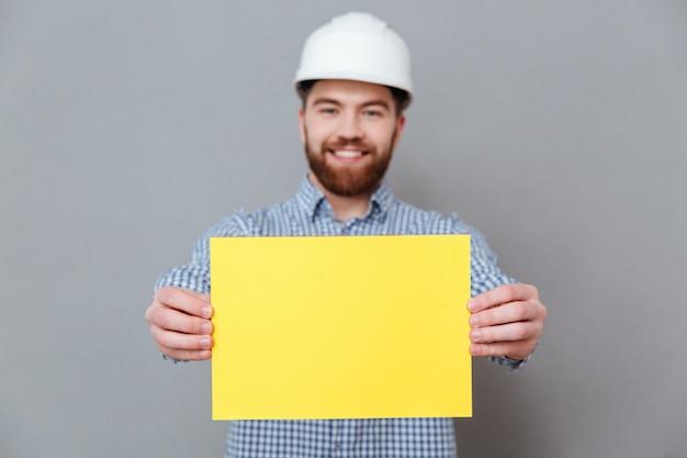 Construtor de homem barbudo mostrando papel em branco