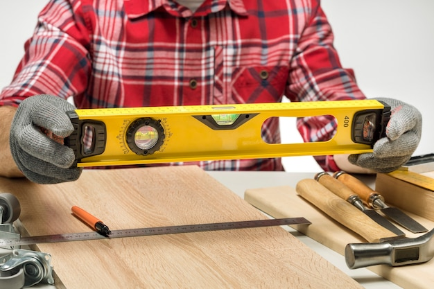 Construtor de homem com nível e ferramentas de trabalho na mesa.