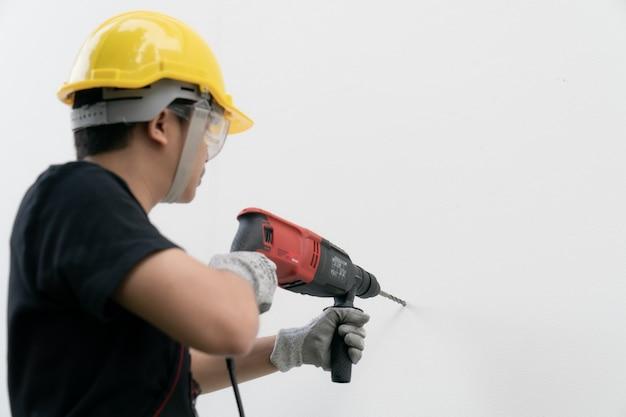 Construtor de homem ou trabalhador com capacete amarelo e máquina de perfuração de óculos de proteção na parede branca.