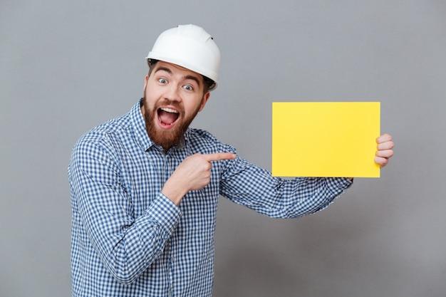 Construtor de jovem barbudo atraente segurando papel em branco