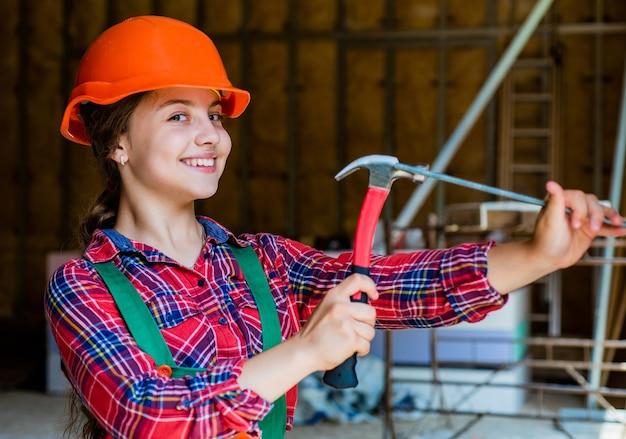Construtor de menina adolescente no martelo de uso de capacete protetor, reparo.