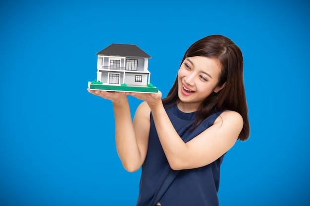 Construtor de mulher asiática, segurando o modelo em casa, isolado no fundo azul