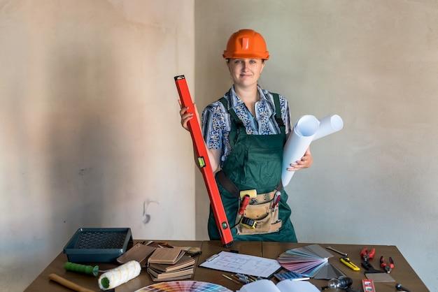 Construtor de mulher com plantas em rolos e mesa de trabalho