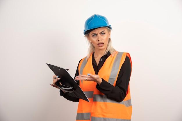 Construtor de mulher descontente, apontando na área de transferência. foto de alta qualidade