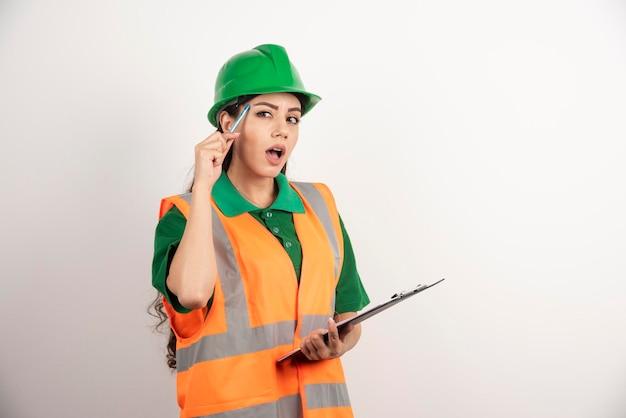 Construtor de mulher se perguntando com a área de transferência em fundo branco. foto de alta qualidade
