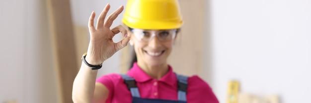 Construtor de mulher sorrindo e mostrando o gesto de ok na oficina. grande seleção de conceito de materiais de construção