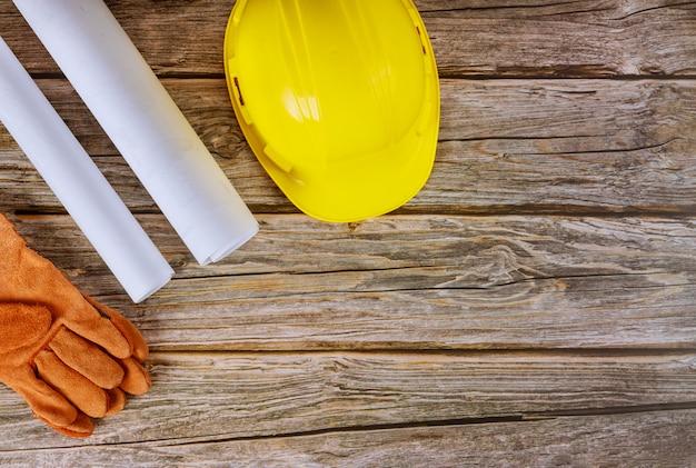 Construtor de projetos de arquitetos, trabalhando na engenharia de planos de construção de escritório, luvas de segurança no capacete amarelo