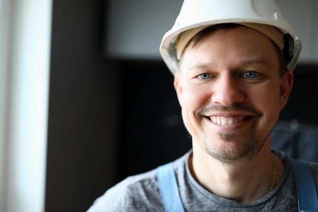 Construtor de rosto feliz em um capacete no local de trabalho