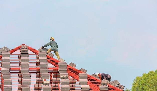 Construtor de telhados instalando telhas no canteiro de obras