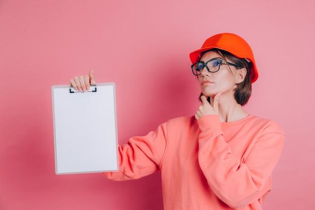 Construtor de trabalhador mulher muito pensativo segurar placa de sinal branco em branco contra fundo rosa. capacete de construção.