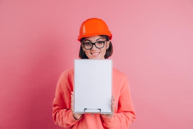 Construtor de trabalhador mulher sorridente segura placa de sinal branca em branco contra um fundo rosa. capacete de construção.