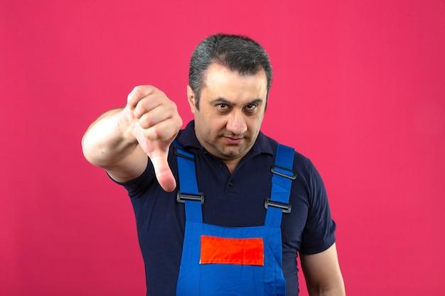 Construtor descontente envelhecido médio homem vestindo uniforme de construção mostrando os polegares para baixo sobre parede rosa isolada