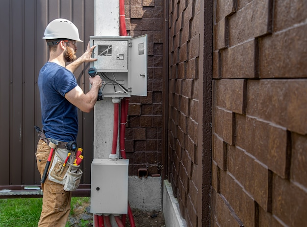 Construtor eletricista no trabalho, examina a conexão do cabo na linha elétrica na fuselagem de um painel de distribuição industrial. profissional de macacão com ferramenta de eletricista.
