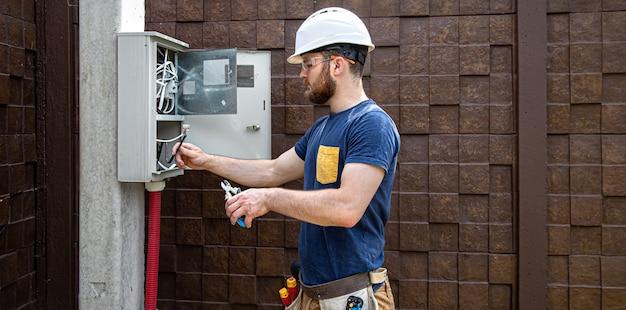 Construtor eletricista no trabalho, examina a conexão do cabo na linha elétrica na fuselagem de um painel de distribuição industrial.