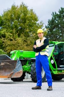 Construtor em frente a maquinaria de construção