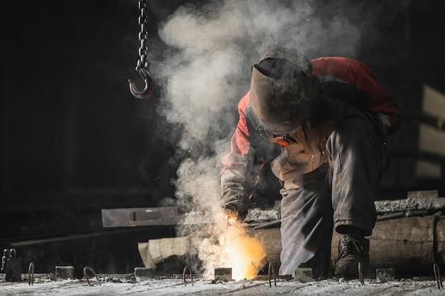 Construtor em uniforme marrom, máscara de soldagem e couro de soldador. soldar o metal com uma máquina de solda a arco, faíscas amarelas voam para os lados